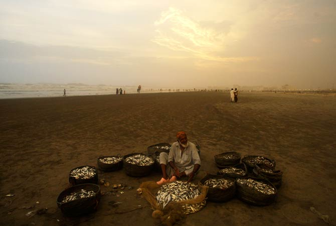 Noor Jan, a fisherman waits for customers at to sell his catch. ? Photo by AP