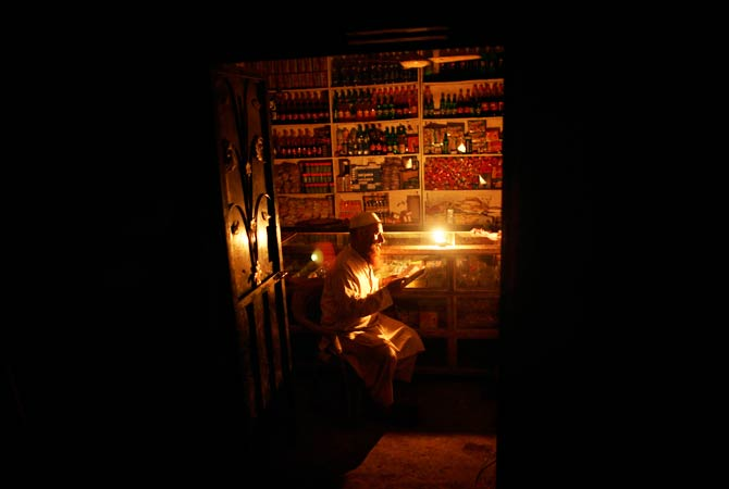 A Pakistani man uses a candle to light his grocery store due to a power cut reads. ? Photo by AP