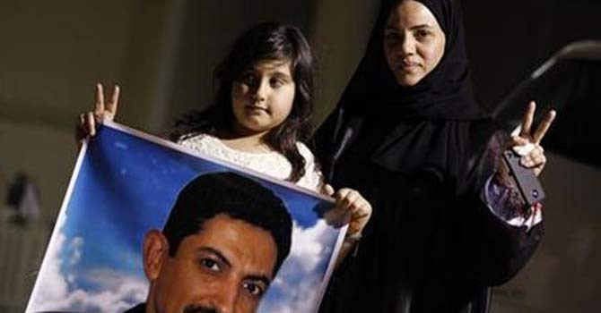 Arrested human rights activist Nabeel Rajab's wife Sumaya and daughter Malak hold a picture of jailed uprising leader Abdulhadi al-Khawaja during a protest demanding Rajab's release. — Reuters Photo