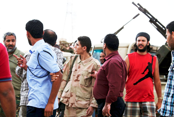 Members of the Rafallah Sahati Islamic Militia Brigades, argue with a Libyan policemen, second left, regarding a request for the militia to evacuate their base.