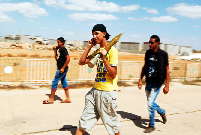 A youth, with a rocket-propelled grenade (RPG) shell, uses his mobile phone as he walks out of the Rafalla al-Sihati brigade base, part of the Libyan army, after it was attacked by demonstrators.