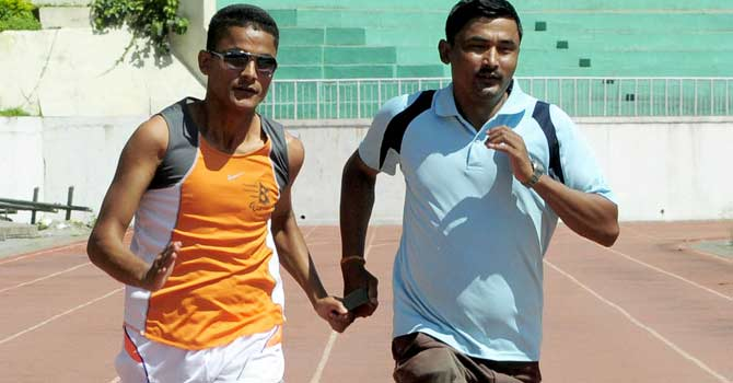 Nepalese athlete Bikram Bahadur Rana (C) trains with partner Maiya Bishankhe (R) at Dashrath Stadium in Kathmandu. Bikram Bahadur Rana on September 4, 2012 set a new personal best at the Paralympics, capping an extraordinary journey to the British capital from the Himalayan nation where he was blinded by Maoist rebels. – Photo by AFP