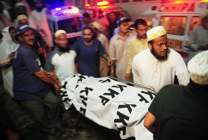 People carry the body of a blast victim to a hospital.