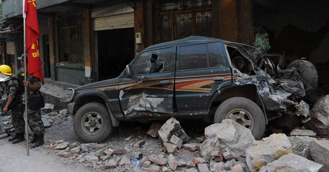 A damaged vehicle lies by the side of a street in Yiliang on September 8, 2012,