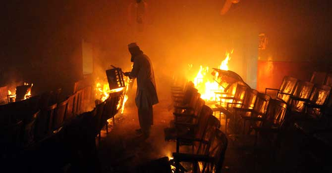 A demonstrator carries material inside a burning cinema during a protest against an anti-Islam film in Peshawar on September 21, 2012. – Photo by AFP