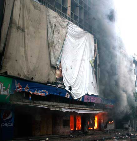 "A cinema burns in Karachi, Pakistan on Friday, Sept 21, 2012. ""We had erected a sign signifying our commitment and fidelity to the protest. We took down film posters and publicity,"" said owners. – Photo by AFP"