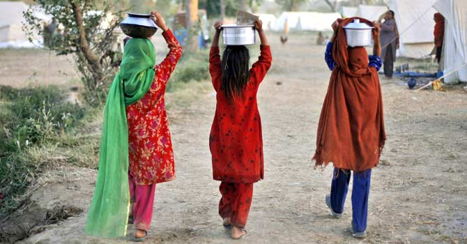 Pakistani girls carry food back to their tents after a food handout at the Jalala  refugee camp near Mardan, in northwest Pakistan, Friday, May 15, 2009.  – File photo by AP