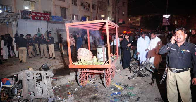 officials scan the site of a bomb explosion in Karachi. – Photo by AFP