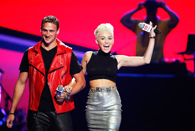 Olympic swimmer Ryan Lochte (L) and singer Miley Cyrus come onstage to introduce a performance.