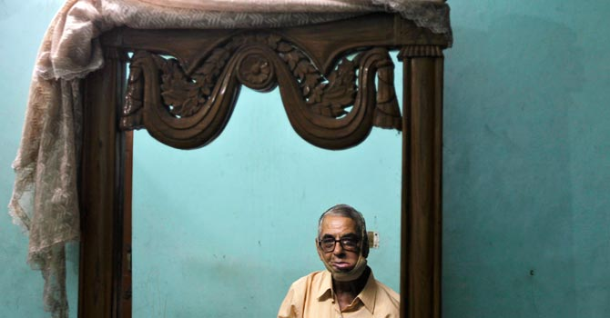 Sixty-eight-year-old Navin Khanna, an oral cancer survivor who said has consumed gutka for almost six years until doctors detected cancer in his mouth, sits in front of a mirror at his home. – Photo by Reuters