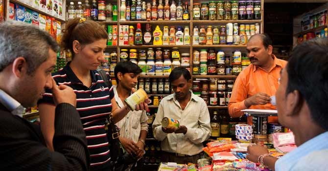 Customers check canned food products at a market  in New Delhi, India, Tuesday,  Sept. 18, 2012. India agreed Friday to open its huge market to foreign retailers such as Wal-Mart as part of a flurry of economic reforms aimed at sparking new growth in the country's sputtering economy. — Photo by AP