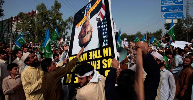 Angry protesters strike a poster showing a portrait of US President Barack Obama during a demonstration against the anti-Islam film. – Photo by AP