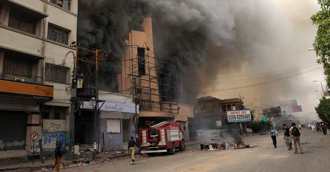 Policemen look on as banks and cinema complex set on fire by an angry mob protesting against an anti-Islam film burns Karachi on September 21, 2012. – Photo by AFP