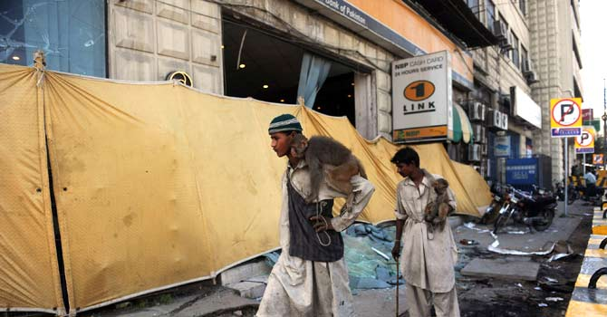Monkey handlers walks past a burnt-out bank following violent protests against an anti-Islam film in Karachi on September 22, 2012 – Photo by AFP