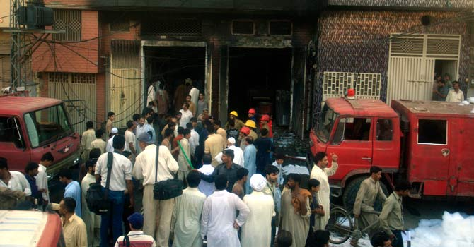 People stand as rescue work is carried out at the factory where fire broke out in Lahore. – Photo by AP