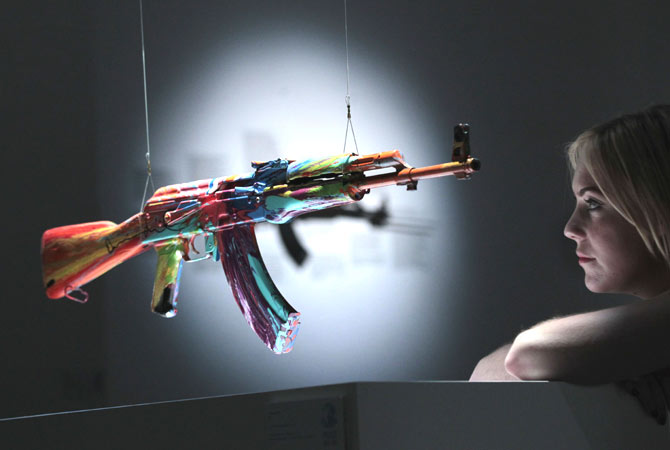 A member of staff poses with an interpretation of an AK-47 assault rifle ?Spin AK47 for Peace One Day? by British artist Damien Hirst on display in an exhibition 'AKA Peace' at the Institute of Contemporary Arts in London, Wednesday, Sept. 26, 2012.