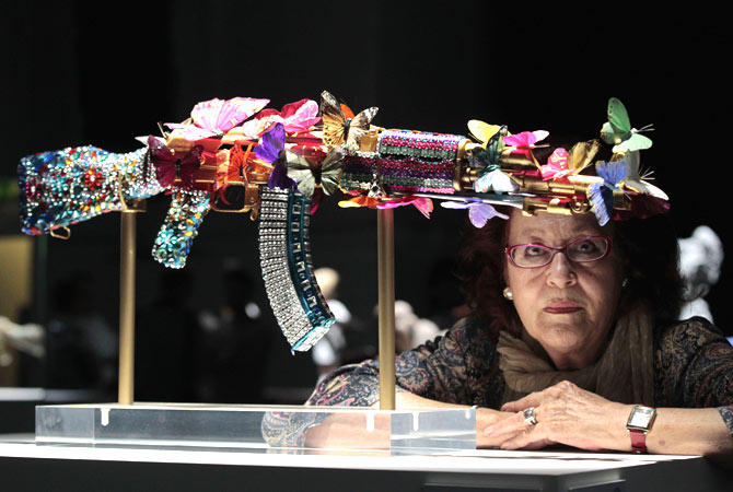 Gaza-born Palestinian artist Laila Shawa poses by her interpretation of an AK-47 assault rifle ?Where Souls Dwell? on display in an exhibition 'AKA Peace' at the Institute of Contemporary Arts in London, Wednesday, Sept. 26, 2012.