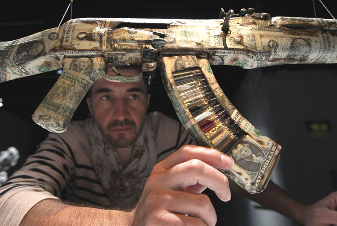 British artist Bran Symondson poses by his interpretation of an AK-47 assault rifle ?Commodities? on display in an exhibition 'AKA Peace' at the Institute of Contemporary Arts in London, Wednesday, Sept. 26, 2012.