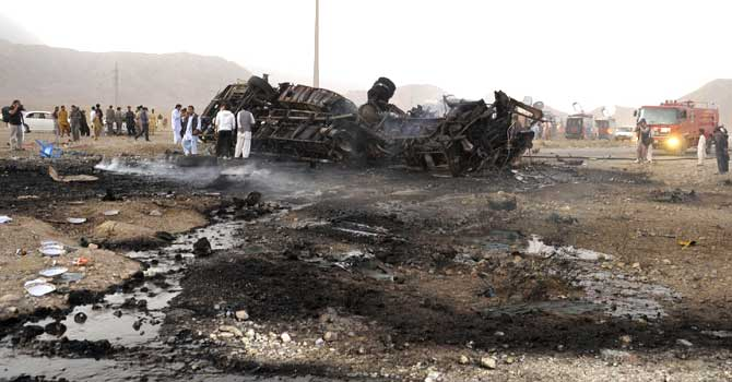 Volunteers search for blast victims in the wreckage of a destroyed passenger bus following a bomb explosion in Mastung district, about 25 kilometres south of Quetta. – Photo by AFP