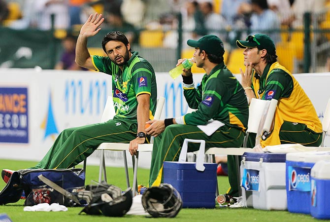 Shahid Afridi, left, waves to his fan as sits on the bench. Afridi could not play in the second ODI due to a back injury. -Photo by AP