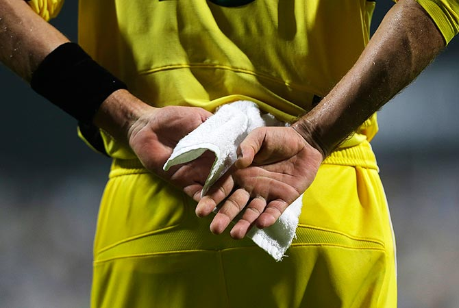 Australia's Michael Hussey dries off his hands with a towel in the hot, humid weather. -Photo by AP