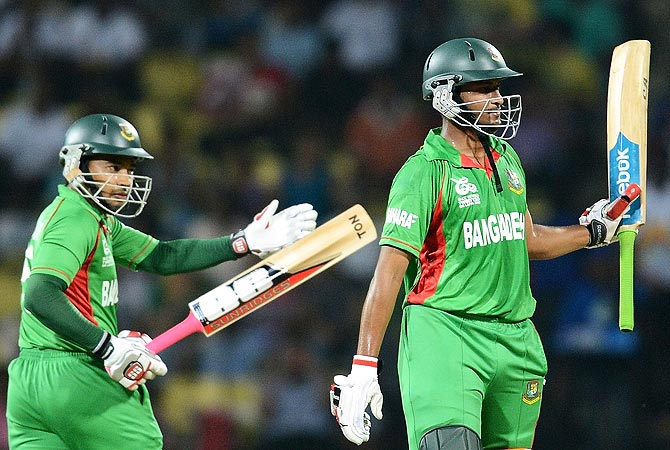 Mushfiqur Rahim (L) applauds as Shakib Al Hasan celebrates his half century. -Photo by AFP