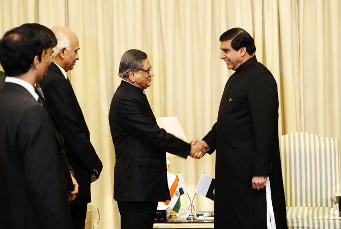 Indian Foreign Minister S.M. Krishna (2R) shakes hands with Pakistani Prime Minister Raja Pervez Ashraf (R) on his arrival for a meeting in Islamabad on September 7, 2012.