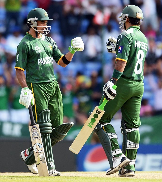 Pakistan cricketer Imran Nazir congratulates Mohammad Hafeez (R) after hitting a six. -Photo by AFP