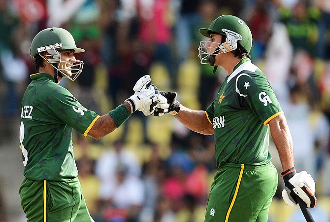 Mohammad Hafeez (L) congratulates Nasir Jamshed for scoring a half century. -Photo by AFP