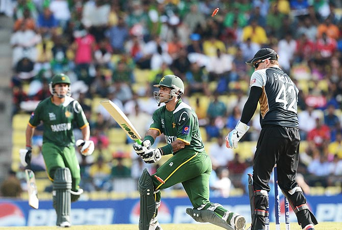 A bail flies up as Pakistan cricket captain Mohammad Hafeez (C) is clean bowled by New Zealand bowler James Franklin. -Photo by AFP