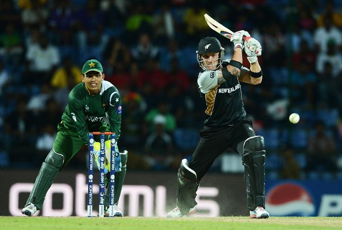 Pakistan wicket keeper Kamran Akmal (L) watches as New Zealand batsman Brendon McCullum plays a shot. -Photo by AFP