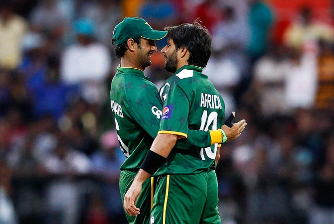 Pakistan's Shahid Afridi (R) is  congratulated by Shoaib Malik after he took the wicket of New Zealand's Rob Nicol. -Photo by Reuters