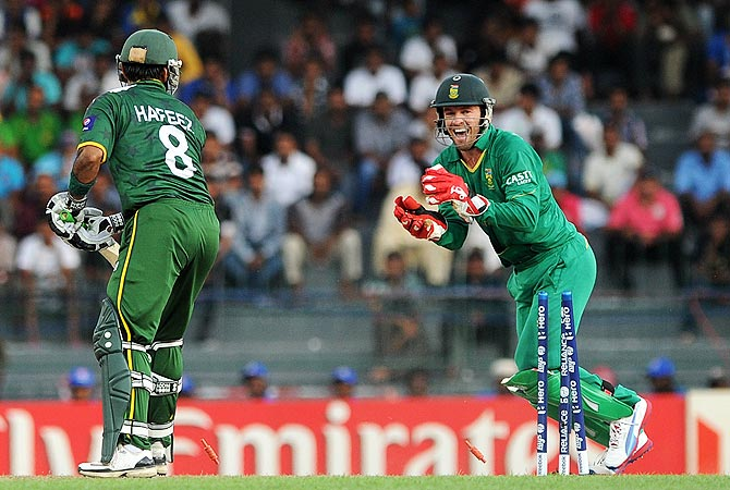 South African wicketkeeper AB de Villiers (R) celebrates the stumping of Mohammad Hafeez. -Photo by AFP