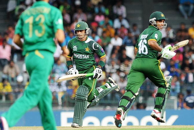 Pakistan cricket captain Mohammad Hafeez (C) and Imran Nazir (R) run between wickets. -Photo by AFP