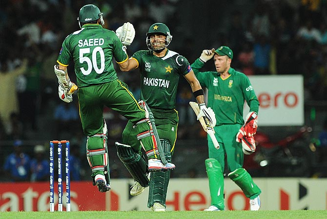 Pakistan cricketers Umar Akmal (C) and Saeed Ajmal (L) celebrate victory as South African captain AB de Villiers (L) looks on. -Photo by AFP