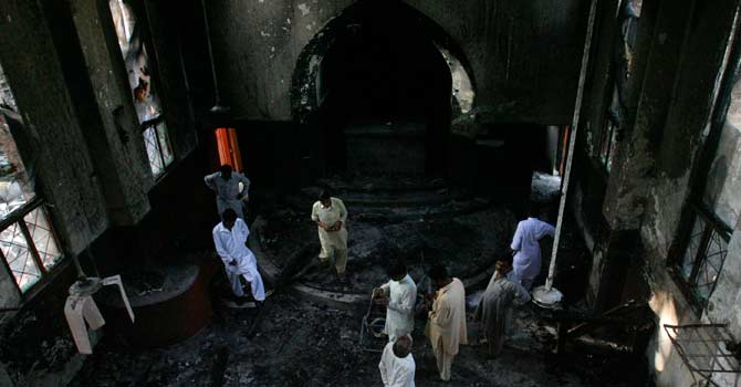 Locals gather inside the Paul Lutheran Church, which was set on fire by a mob during an anti-Islam film protest a day earlier, in Mardan. – Photo by Reuters
