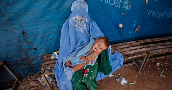 An Afghan refugee woman waits her turn to receive a drop of polio vaccine for her child at the United Nations High Commissioner for Refugees (UNHCR) supported Jalozai camp on the outskirts of Peshawar. -Reuters Photo