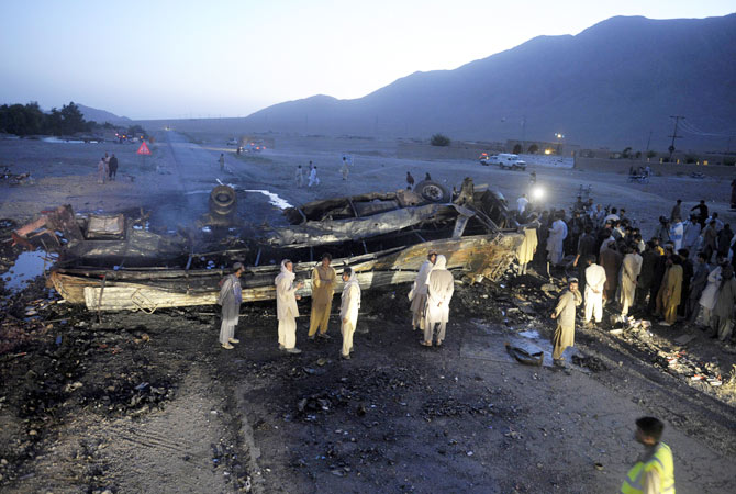 Pakistani security officials and local residents gather beside the wreckage of a destroyed passenger bus following a bomb explosion in Mastung district, about 25 kilometres south of Quetta, the capital of Balochistan province on September 18, 2012.