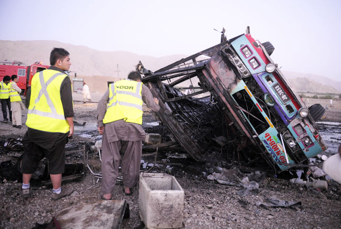 Volunteers search for blast victims in the wreckage of the destroyed passenger bus.