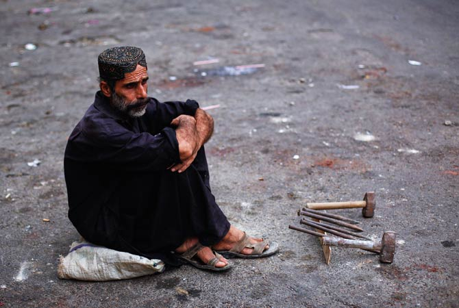 A day laborer sits near his tools as he waits for work along a road early in the morning. ? Photo by Reuters