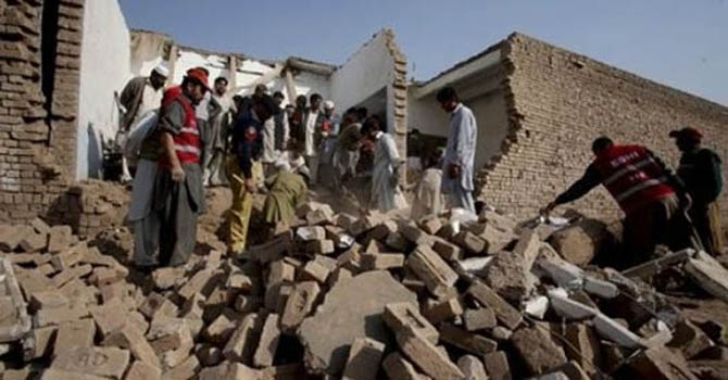 Pakistani police officers and rescue worker survey the damaged portion of a school caused by a bomb blast. - File Photo.