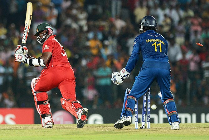 Zimbabwe's cricketer Hamilton Masakadza (L) is bowled out by Sri Lankan cricketer Ajantha Mendis. -Photo by AFP