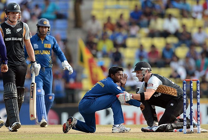New Zealand cricketer Brendon McCullum (R) tends to Sri Lanka bowler Akila Dananjaya (2R). -Photo by AFP
