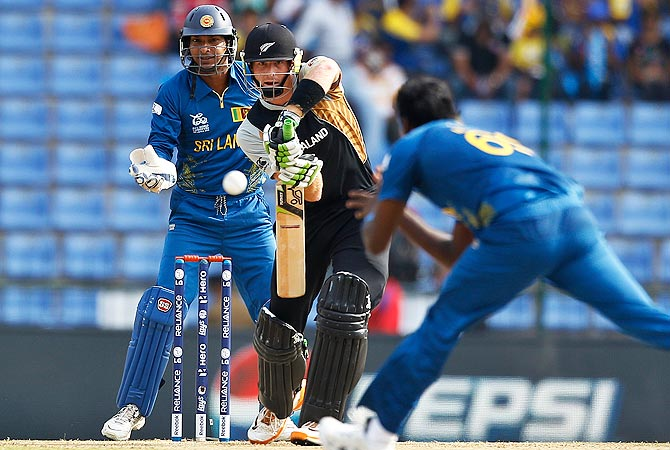 Sri Lanka's wicketkeeper Kumar Sangakkara, left, watches New Zealand's batsman Martin Guptill, center, play a shot. -Photo by AP