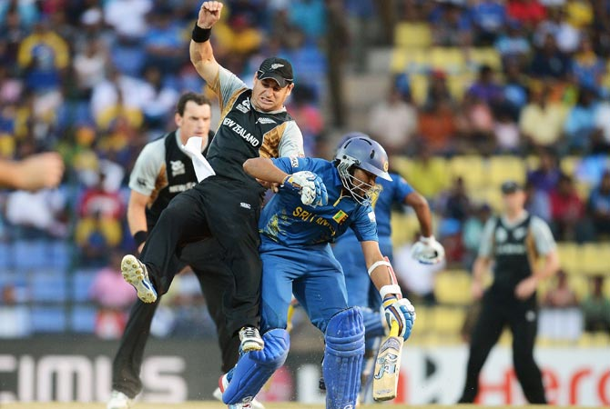 New Zealand cricketer Nathan McCullum (L) collides with Sri Lankan cricketer Tilakaratne Dilshan. -Photo by AFP