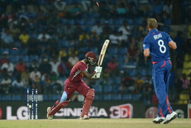 Bails go up in the air as England cricketer Stuart Broad (R) clean bowls West Indies cricketer Darren Sammy.