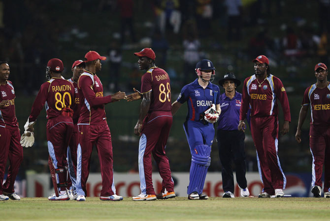 West Indies' players celebrate their win as England's Eoin Morgan (4th R) leaves the field.