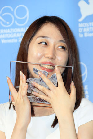 Director Wang Bing with her Orizzonti Best Film award for 'San Zimei' at the awards photo call.