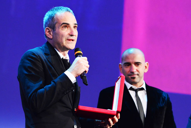 French film director Olivier Assayas holds the Prize for the Best Screenplay.
