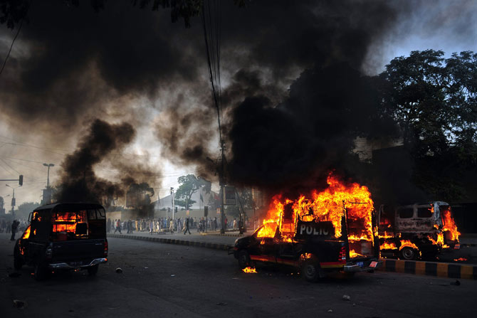 Smoke and flames rise from burning police vehicles torched by angry demonstrators during a protest against an anti-Islam film in Karachi on September 21, 2012.